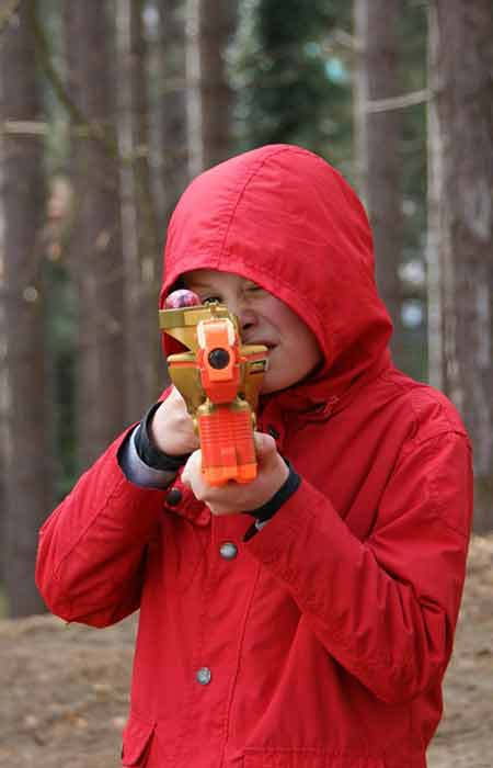 Jongen met rode jas richt lasergeweer