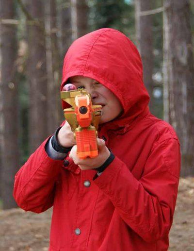 jongen met rode jas speelt lasergame